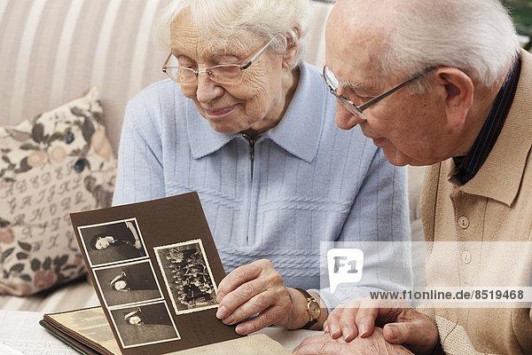 Seniorenpaar beim Betrachten des alten Fotoalbums zu Hause