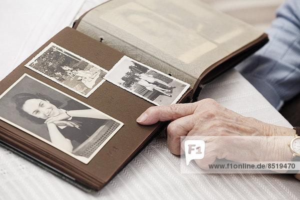 Seniorin beim Betrachten alter Fotos von sich selbst