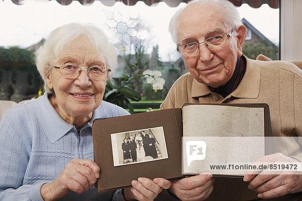 Seniorenpaar zeigt altes Foto vom Hochzeitstag