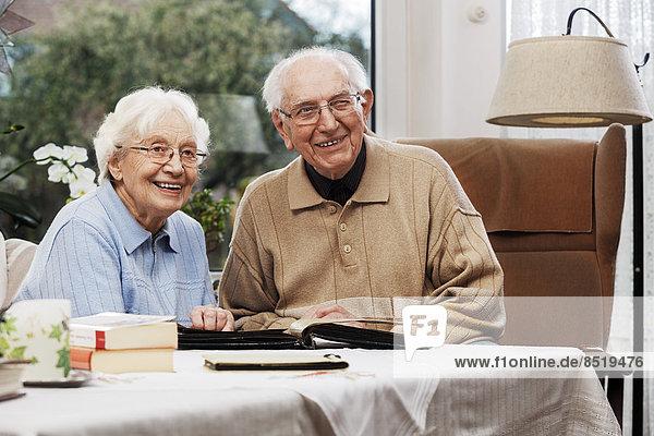 Seniorenpaar beim Betrachten alter Fotos zu Hause