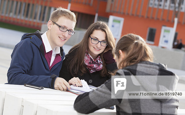 Three students learning together outdoors