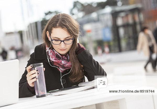 Schüler lesen und hören Musik im Freien