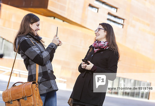 Two young women using digital tablet outdoors