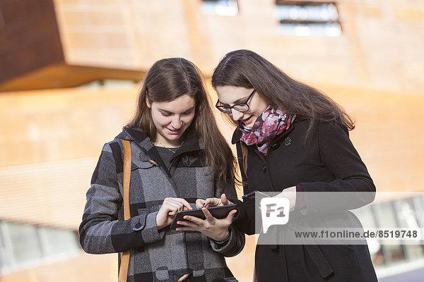 Zwei junge Frauen mit digitalem Tablett im Freien