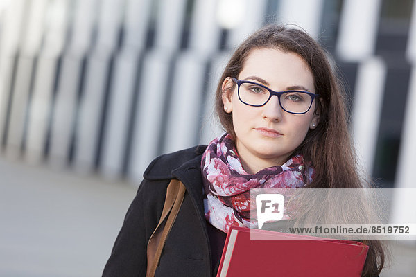 Student with folder outdoors  portrait