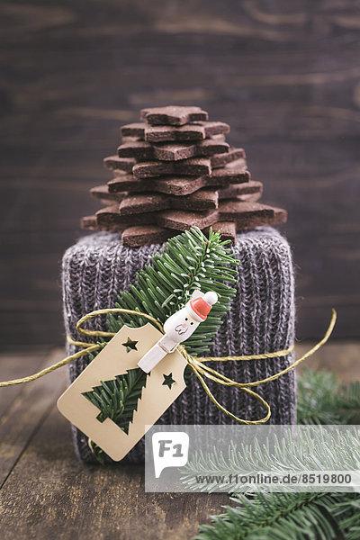 Weihnachtsgeschenk verpackt in gestrickter Geschenkverpackung mit einem Weihnachtsbaum aus Schokoladenzuckerplätzchen
