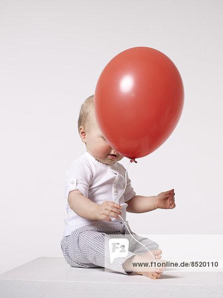 Baby mit rotem Ballon