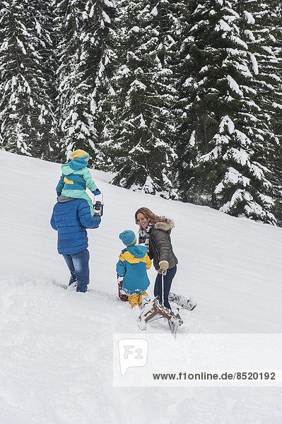 Austria  Salzburg Country  Altenmarkt-Zauchensee  Family walking in snow  pulling sledge