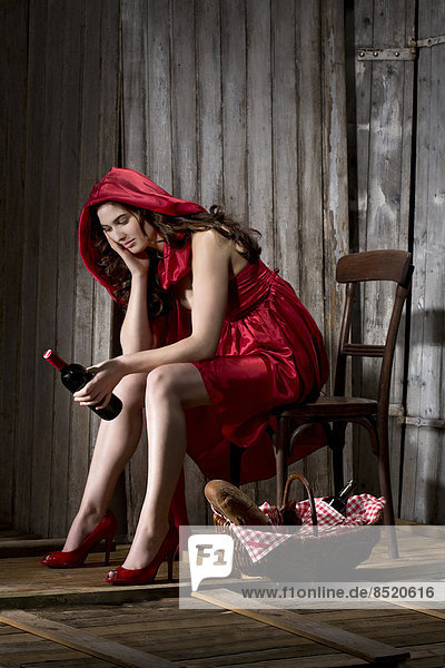 Young woman sitting in a shack dressed as Red Riding Hood  studio shot