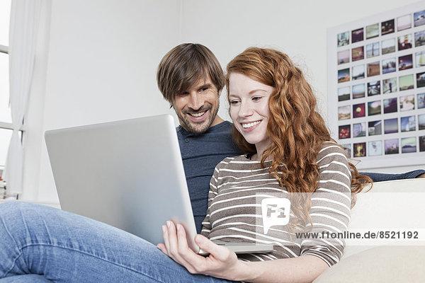 Deutschland  München  Paar sitzend auf Sofa mit Laptop