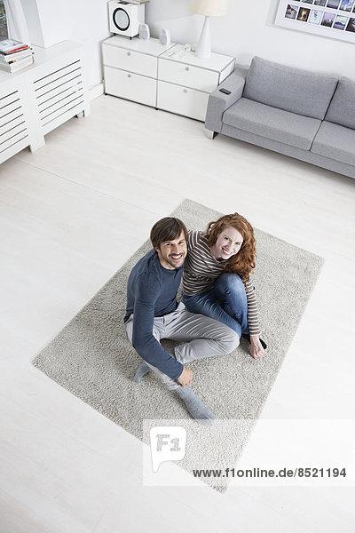 Deutschland  München  Paar sitzend auf dem Boden im Wohnzimmer