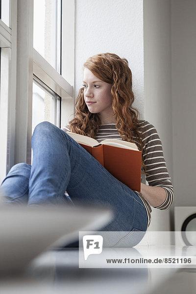 Frau auf Fensterbank sitzend  Lesebuch