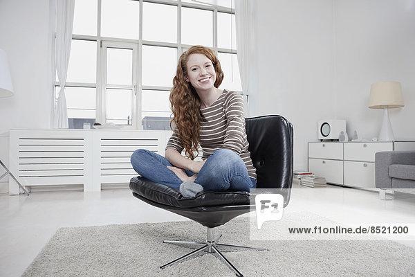 Frau zu Hause  im Schneidersitz sitzend