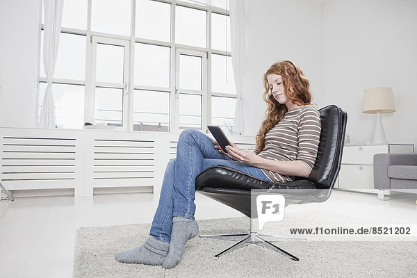 Frau zu Hause  sitzt im Stuhl  liest E-Book