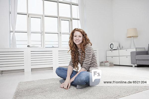 Frau sitzend auf dem Boden im Wohnzimmer