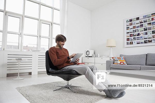 Mann mit digitalem Tablett  im Stuhl sitzend