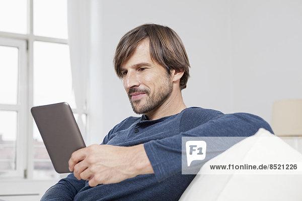Man sitting on sofa  reading e-book