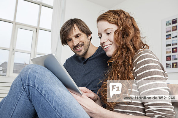 Germany  Munich  Couple sitting on sofa using digital tablet