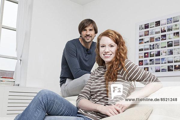 Deutschland  München  Paar auf Sofa sitzend