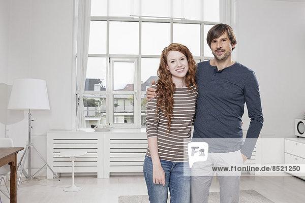 Deutschland  München  Paar zu Hause  Arme um die Ecke