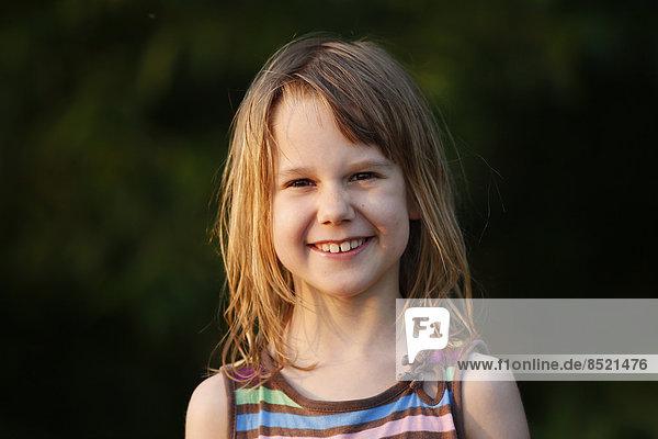 Porträt eines lächelnden kleinen Mädchens bei Sonnenschein