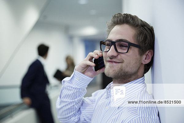 Young business man leaning on wall