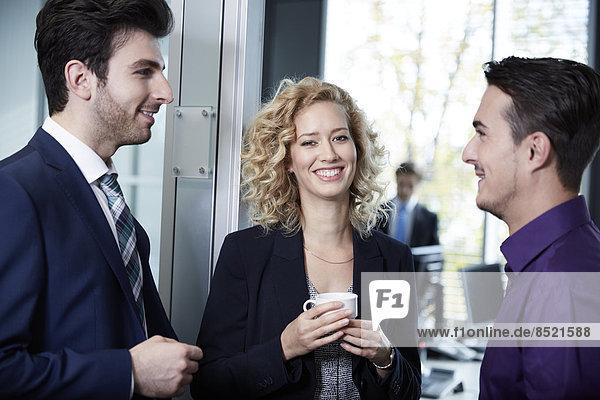 Germany  Neuss  Business people drinking coffee in office