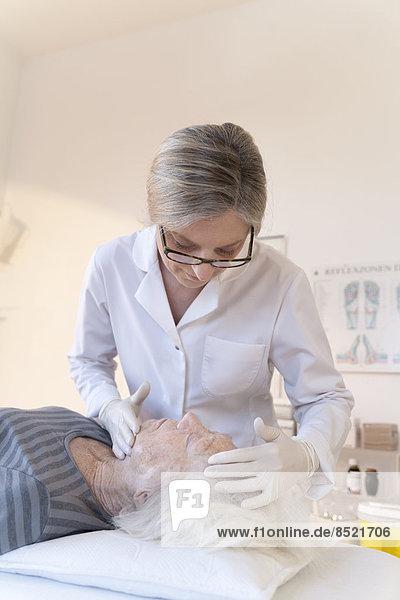 Ärztin in der Alternatiße  die eine ältere Frau behandelt Ärztin in der Alternatiße, die eine ältere Frau behandelt