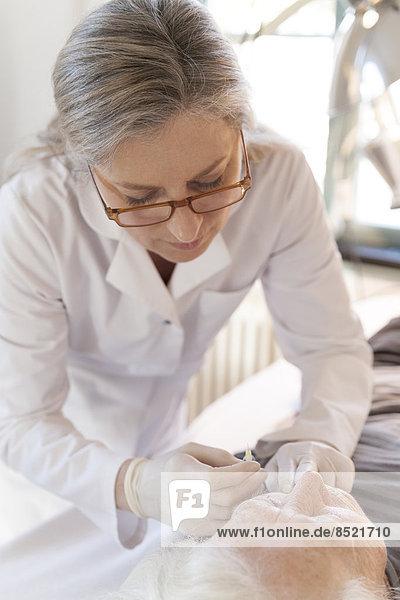Female alternatiße practitioner gißing senior woman injection acupuncture Female alternatiße practitioner gißing senior woman injection acupuncture