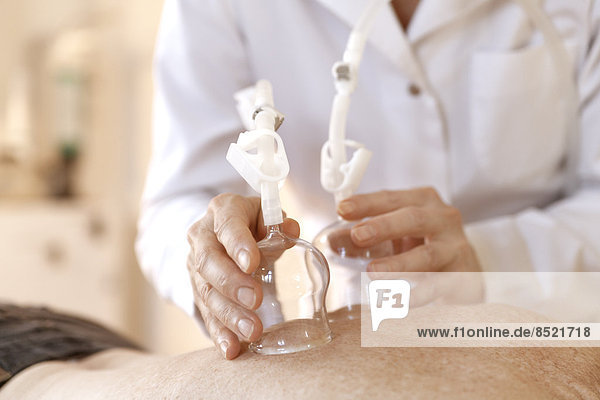 Female alternatiße practitioner treating senior woman with ßacuum cupping therapy Female alternatiße practitioner treating senior woman with ßacuum cupping therapy