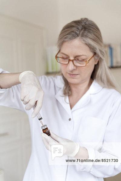 Female alternatiße practitioner preparing injection syringe Female alternatiße practitioner preparing injection syringe