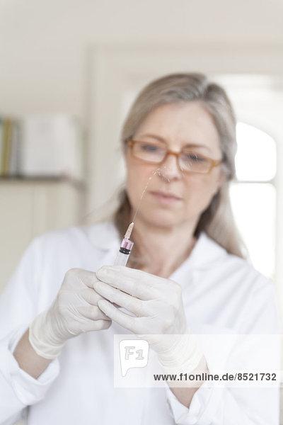 Alternativer weiblicher Praktiker bei der Vorbereitung der Injektionsspritze Alternativer weiblicher Praktiker bei der Vorbereitung der Injektionsspritze