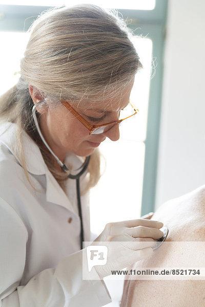 Weibliche Alternatiße Praktizierende auskultierende Seniorenfrau mit Stethoskop Weibliche Alternatiße Praktizierende auskultierende Seniorenfrau mit Stethoskop