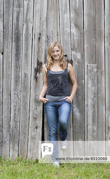 Österreich  Salzkammergut  Mondsee  junge Frau an einer grauen Holzfassade lehnend
