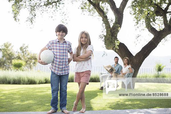 Bruder und Schwester mit Volleyball im Hinterhof
