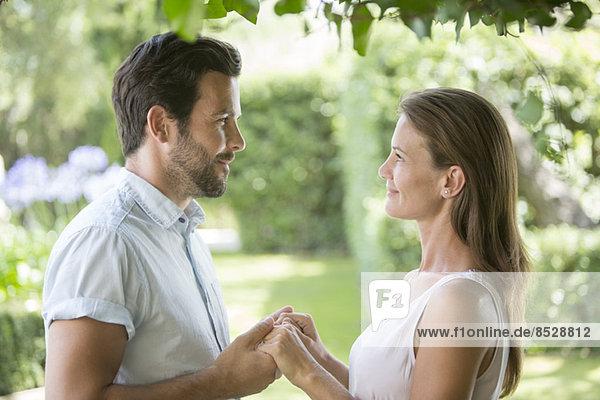Paar hält sich im Garten von Angesicht zu Angesicht an den Händen.