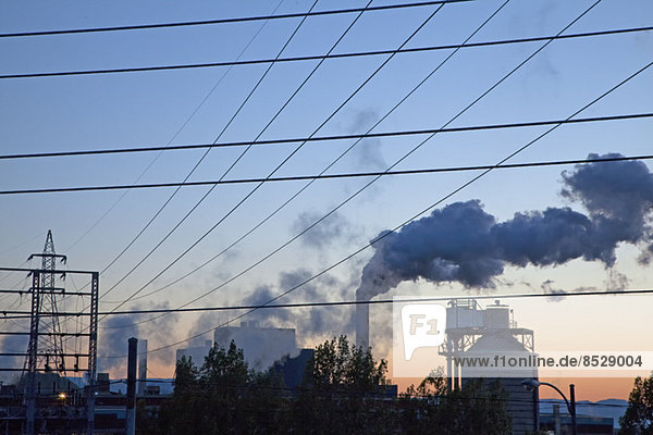 Silhouette des Rauchs  der bei Sonnenaufgang aus der Fabrik austritt.