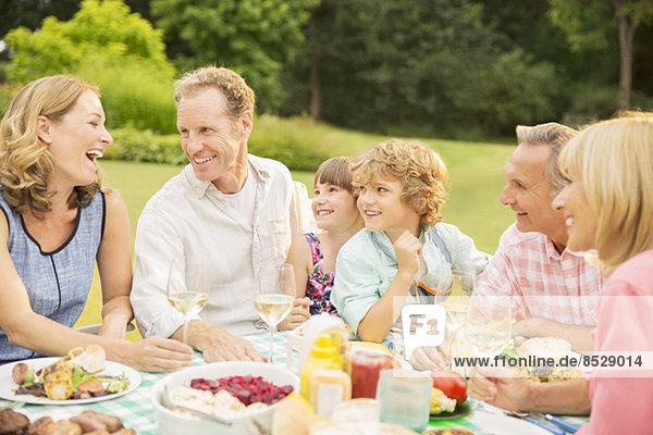 Mehrgenerationen-Familie beim Mittagessen im Garten