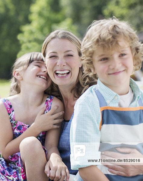 Mutter und Kinder lächeln im Freien