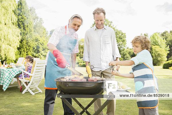 Männer grillen Fleisch auf dem Grill im Hinterhof