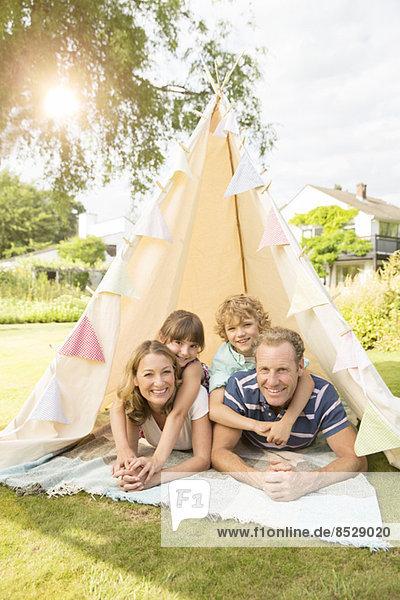 Familie entspannt im Tipi im Hinterhof