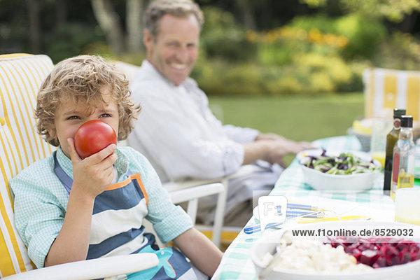 Junge spielt mit Essen am Tisch im Hinterhof
