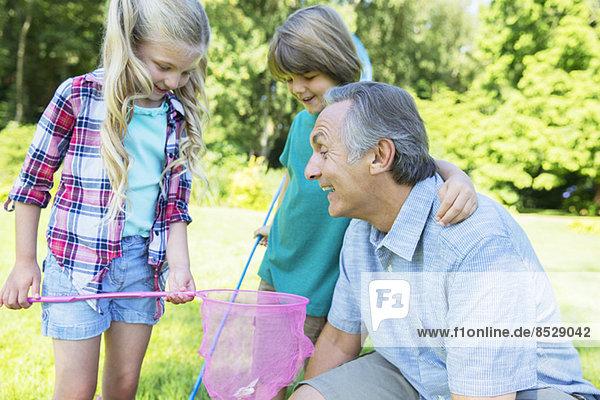 Mann und Enkelkinder beim Spielen im Freien