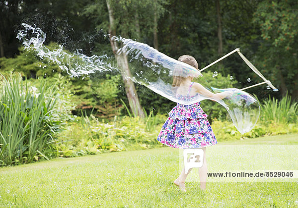 Mädchen macht große Blasen im Garten