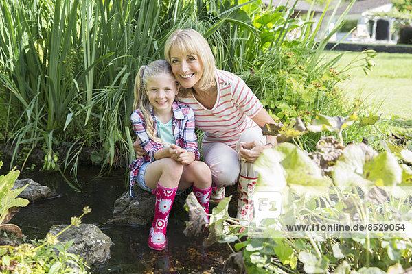 Großmutter und Enkelin lächelnd am Teich