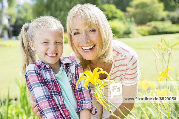 Großmutter und Enkelin lächeln im Garten