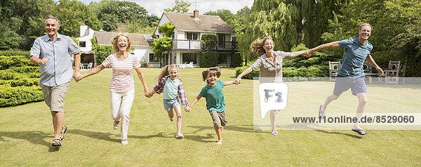 Mehrgenerationen-Familie beim Händchenhalten und Laufen im Gras