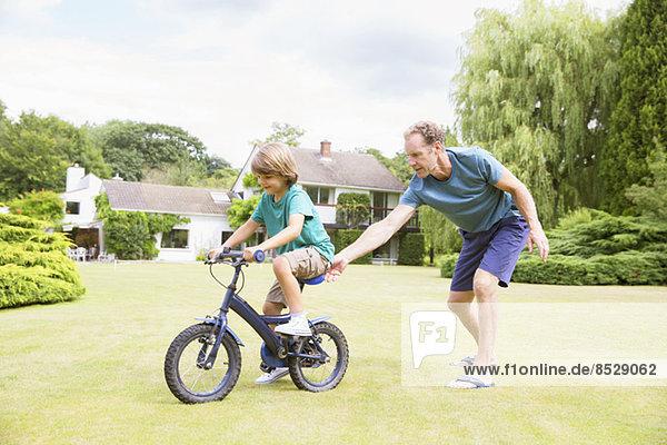 Vater schiebt Sohn auf Fahrrad im Garten