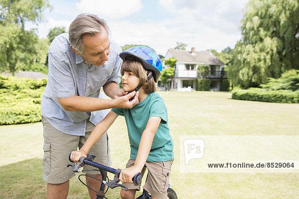 Großvater verstellbarer Fahrradhelm am Enkel