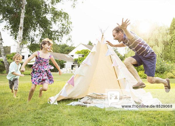Vater jagt Kinder um das Tipi im Garten.